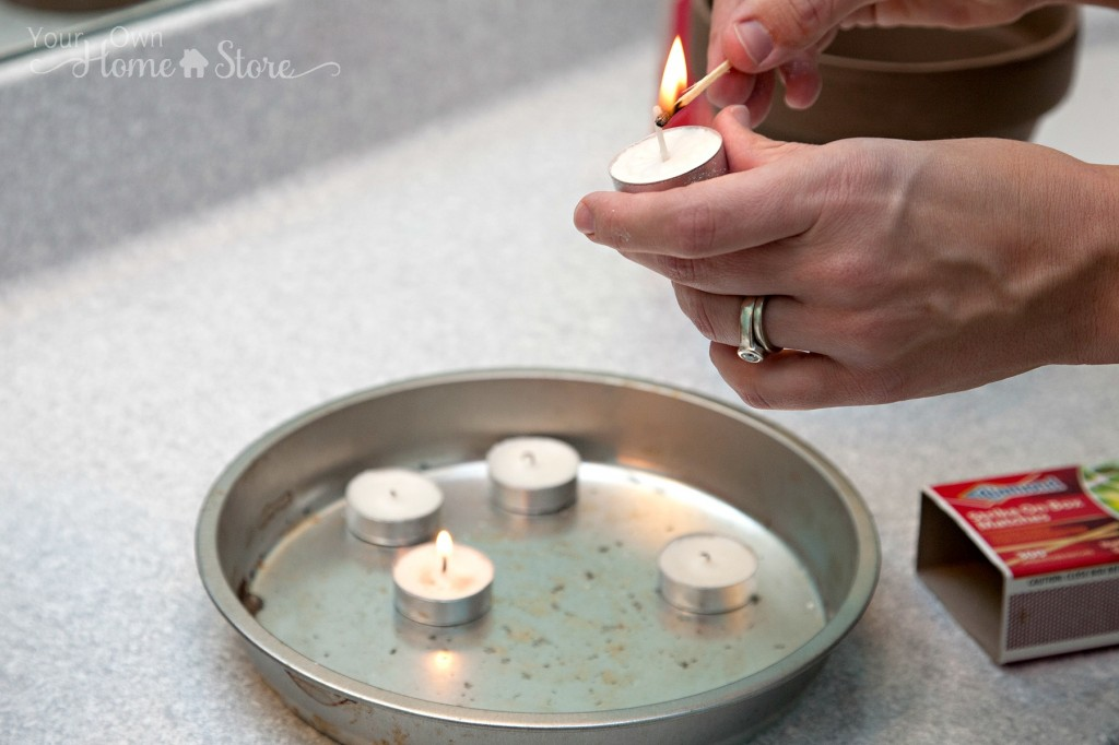 woman lighting tea candles with a match