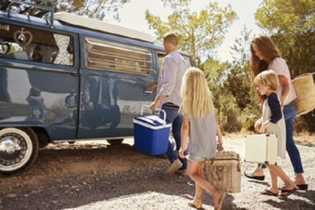 on camping list: Family preparing their camper van for a road trip, side view