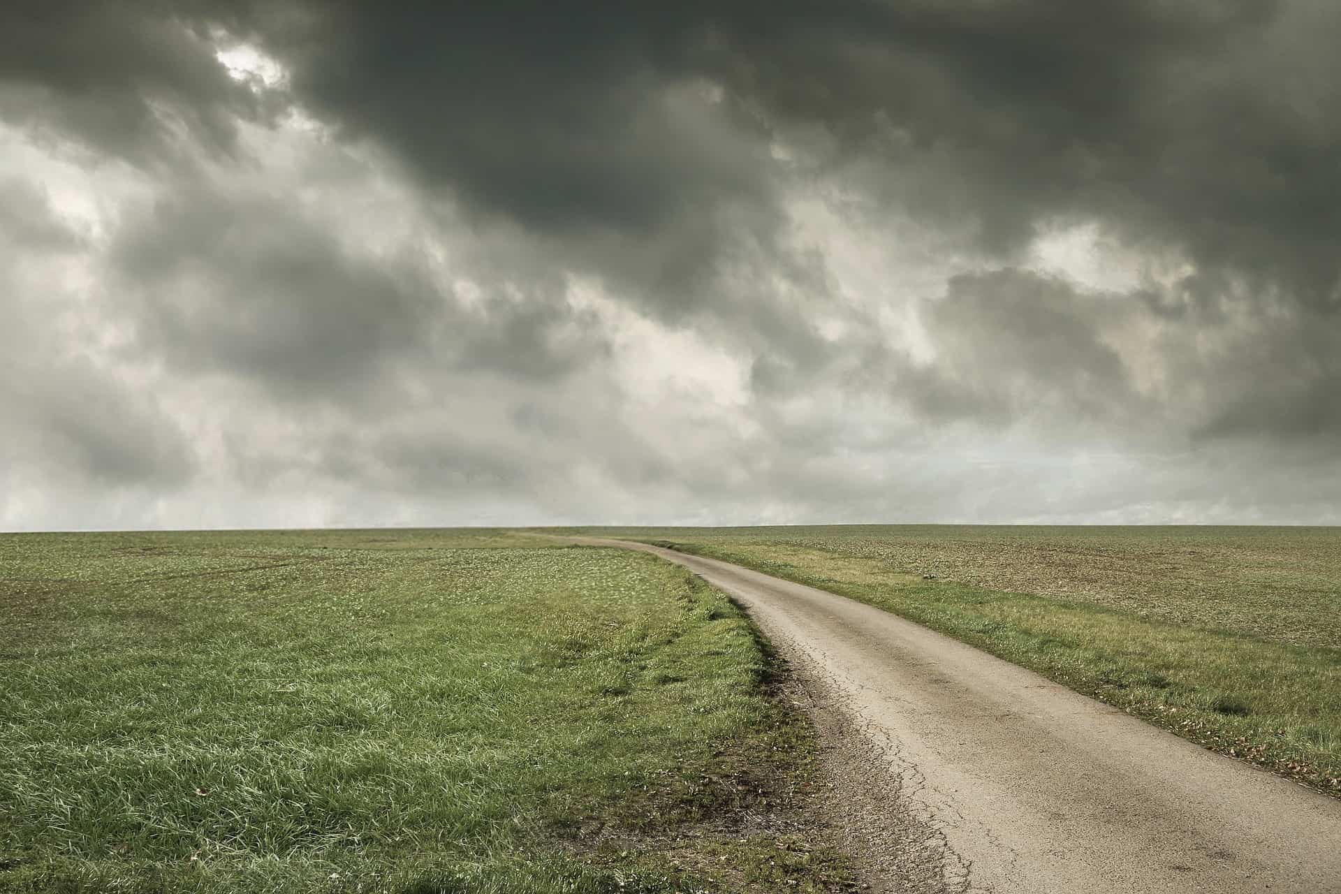 A dirt road with a flat horizon and a stormy sky.