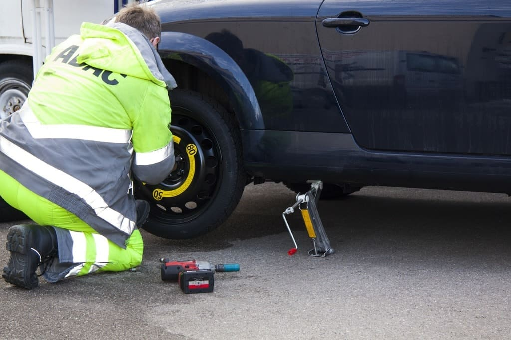 Man using car survival kit to fix and replace a flat tire