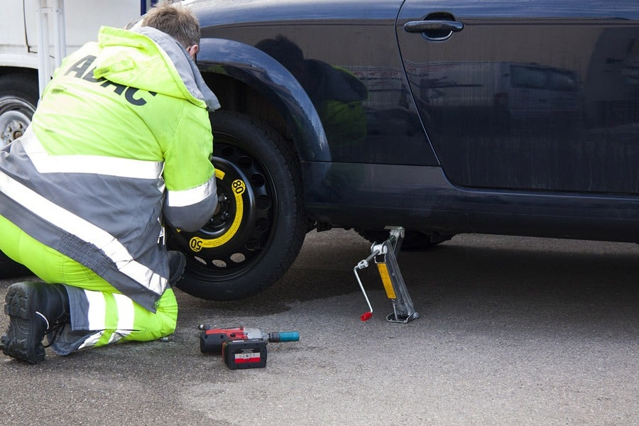 Officer repairing a flat tire car